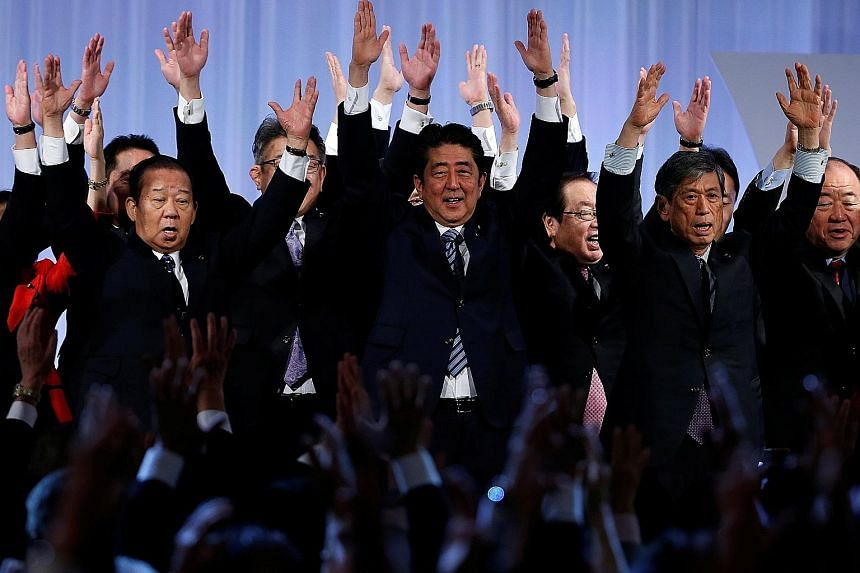 Mr Shinzo Abe (centre) cheering with members of the ruling Liberal Democratic Party during its annual party convention in Tokyo yesterday. The LDP congress has approved extending the limit for its leaders to three consecutive three-year terms, up fro