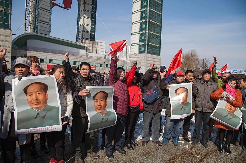 Residents in China's Jilin province with posters of the late communist leader Mao Zedong during a protest yesterday calling for a boycott of South Korean goods. South Korean companies are facing a backlash after the Seoul government secured land for