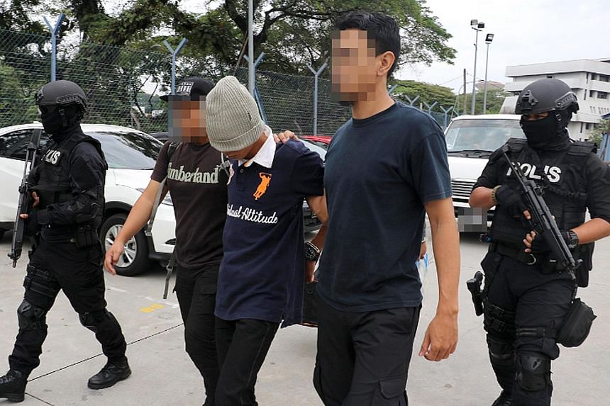 Police leading away a suspect linked to terror groups during a raid in the Klang Valley last month.