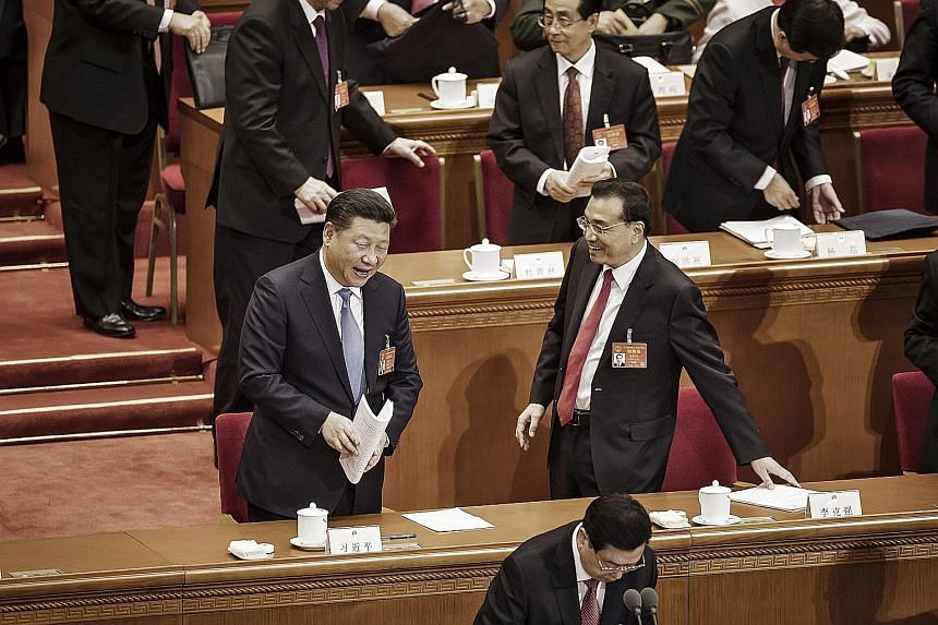 Chinese President Xi Jinping (left) speaking with Premier Li Keqiang following the opening of the National People's Congress, China's Parliament, at the Great Hall of the People in Beijing yesterday. Mr Xi said yesterday that China would continue to