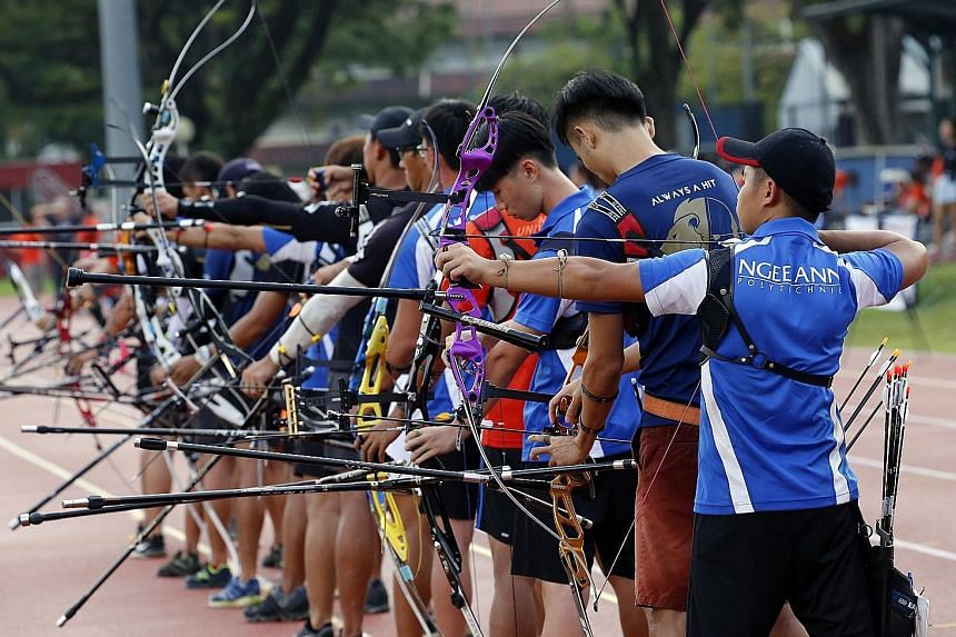 Archers taking aim during the Institutional Archery Competition at the Nanyang Technological University (NTU) Sports and Recreation Centre yesterday. Around 100 participants turned up on the second day of the two-day competition, which is now into it