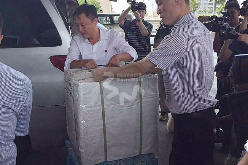 Several pieces of luggage seen being loaded into a grey Toyota Alphard.