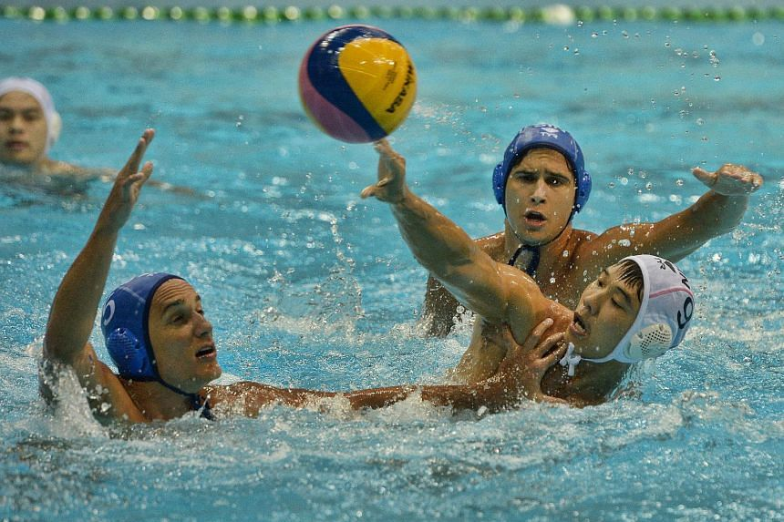 Singapore's Chow Jing Lun (No. 9) squares off with Hungarian club OSC Budapest's Juhasz Zsolt (No. 5) in a friendly match at the OCBC Aquatic Centre on Jan 6, 2016.