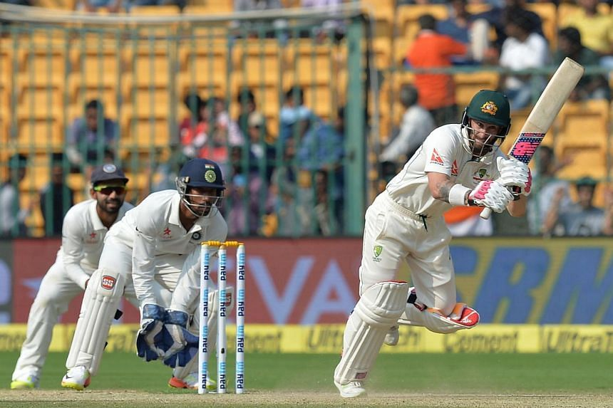 Australian batsman Matthew Wade(right) is watched by India's wicketkeeper Wriddhiman Saha as he plays a shot during the second day of the second cricket Test match between India and Australia on March 5, 2017.