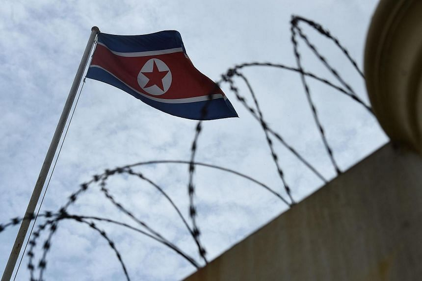 The North Korean flag is seen past a barbed-wire fenced wall of the North Korean embassy in Kuala Lumpur.