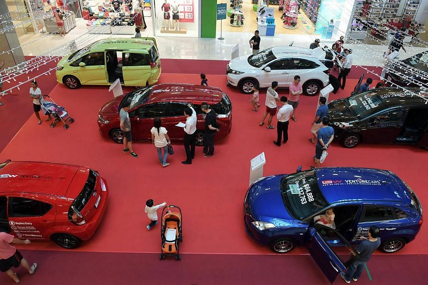 Customers looking at hybrid cars at the VentureCars roadshow at OneKM mall atrium.