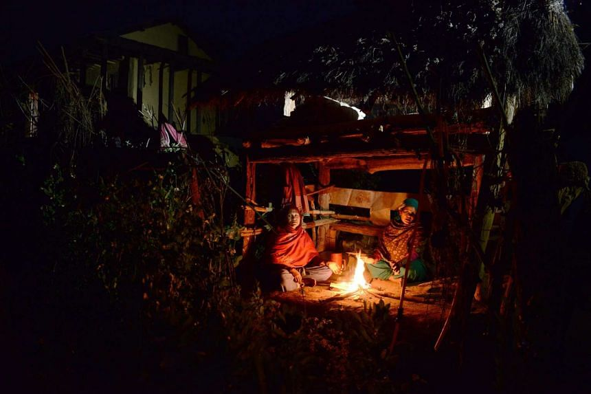 Pabitra Giri (left) and Yum Kumari Giri (right) sit by a fire as they live in a Chhaupadi hut during their menstruation on Feb 3, 2017.