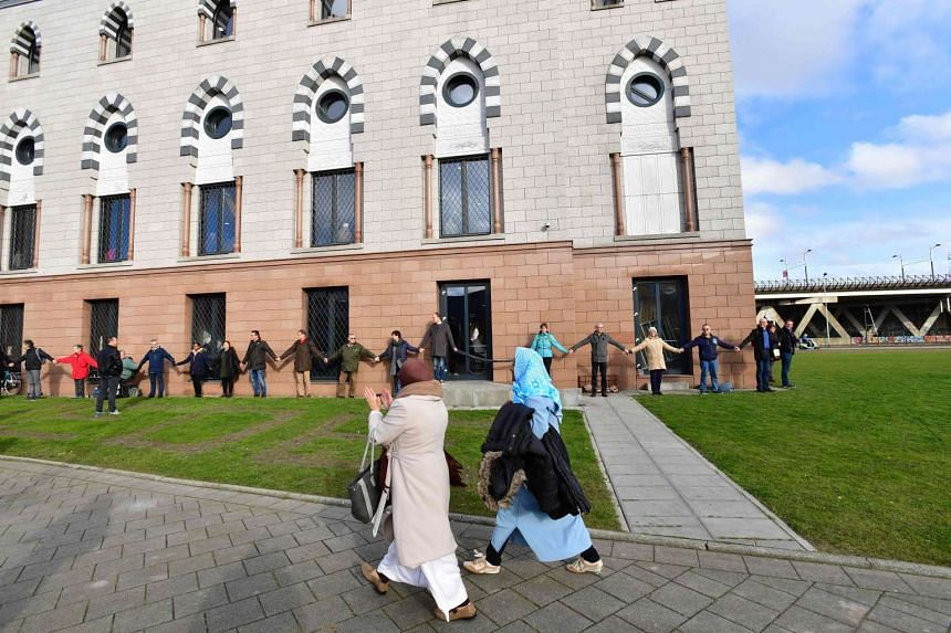 People form a human chain around the Essalam mosque  on Feb 3, 2017 in Rotterdam in the Netherlands.