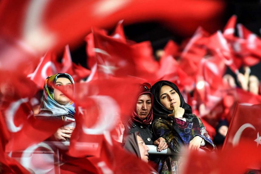 Women are surrounded by supporters waving Turkish national flags on Sunday (Mar 5, 2017) during a pro-government women's meeting.