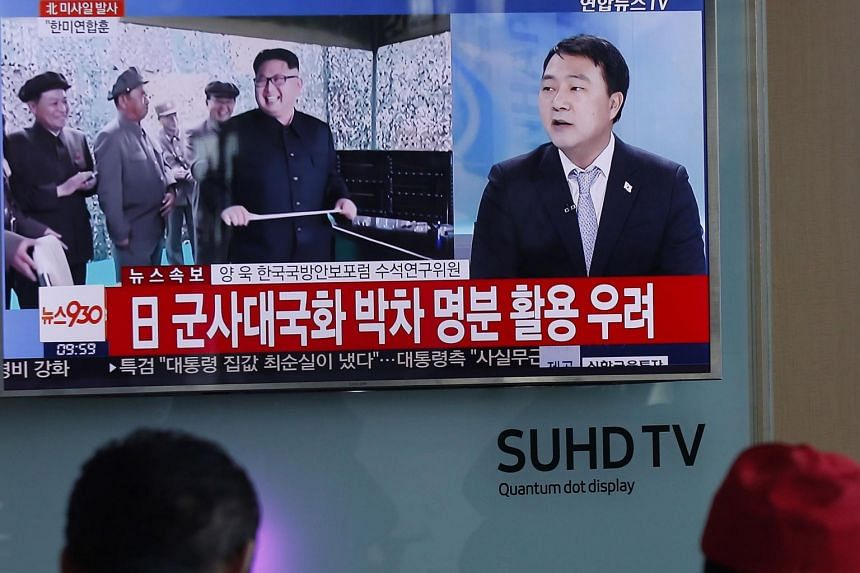 South Koreans watching a new programme reporting on the test-firing of ballistic missiles by North Korea, at a station in Seoul on March 6, 2017.