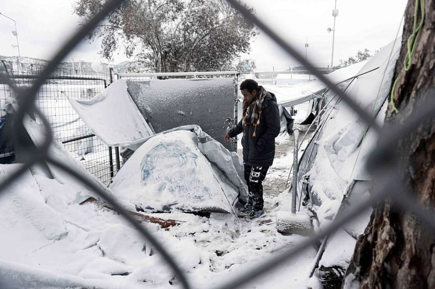 A migrant stands next to a snow-covered tent on the island of Lesbos, on Jan 7, 2017.