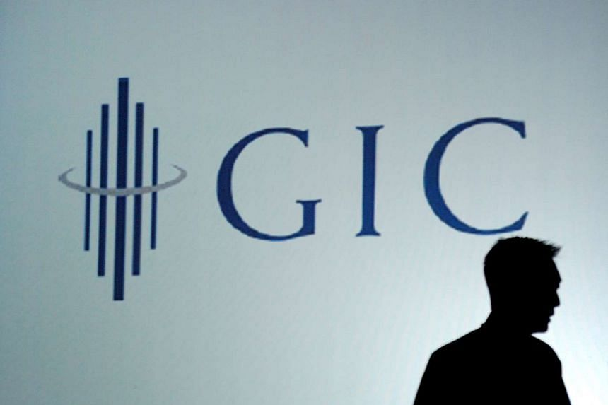 An employee is silhouetted against the logo for the Government of Singapore Investment Corp (GIC).