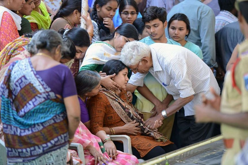 Sunayana Dumala (centre), wife of killed Indian engineer Srinivas Kuchibhotla, is consoled by family members prior to performing the last rites at his funeral in Hyderabad.