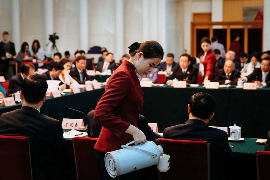 A Chinese hostess pours tea for members of the Chongqing delegation's group discussion during the fifth Session of the 12th National People's Congress at the Great Hall of the People in Beijing, China.
