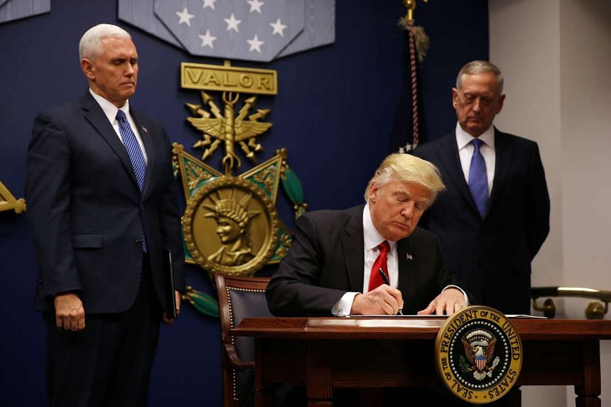 US President Donald Trump signs a revised executive order for a travel ban at the Pentagon in Washington, US.