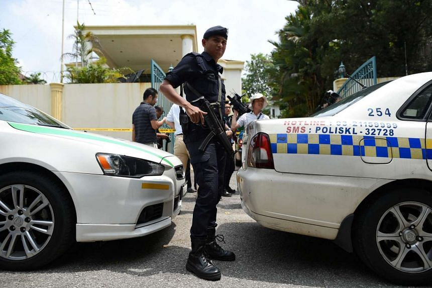 A member of the Royal Malaysian Police keeps watch beside parked squad cars blocking the entrance to the North Korean embassy in Kuala Lumpur.