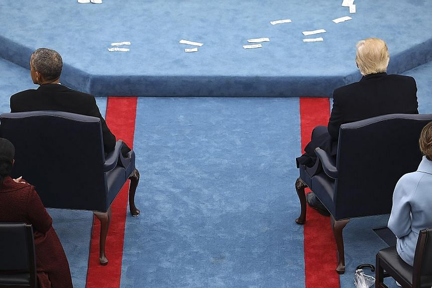 Mr Obama sitting across the aisle from Mr Trump at the presidential inauguration in January. Mr Trump's insistence that his predecessor authorised wiretapping of Trump Tower phones has baffled Washington. The US President has offered no proof to supp