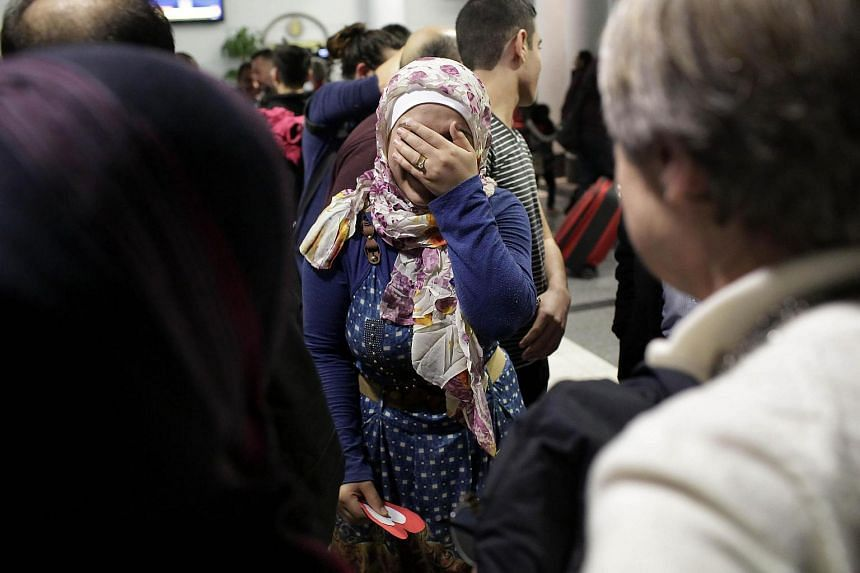 Syrian refugee Baraa Haj Khalaf (centre), covers her face as she reacts to greeting people during her arrival at O'Hare International Airport on Feb 7, 2017 in Chicago.