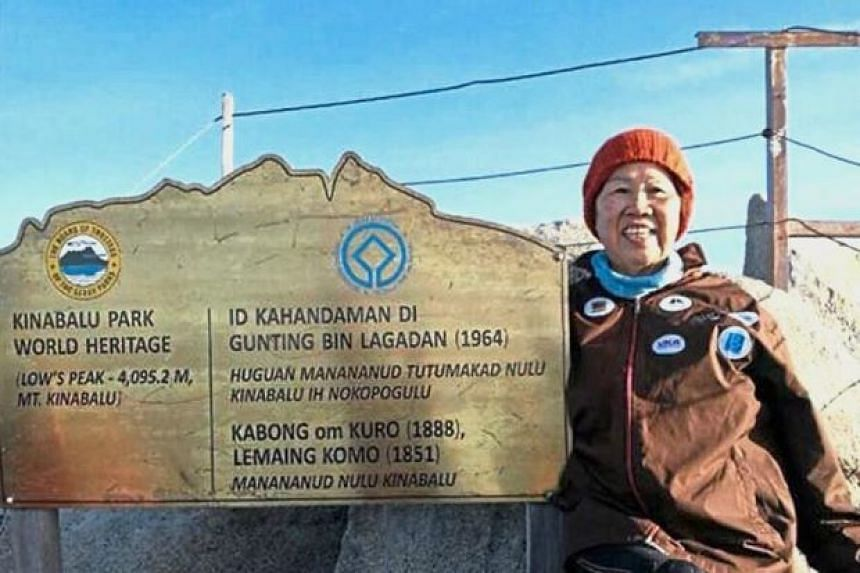 Madam Chee Moy Chun is all smiles as she poses for a photo at the top of Mount Kinabalu after her historic climb.