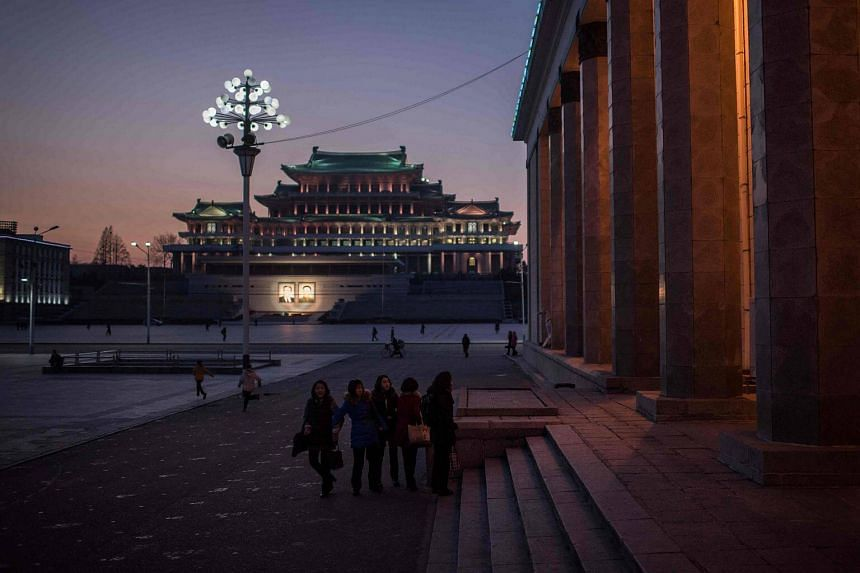 A group of students walk before the steps of the Korean Central History Museum on Kim Il-Sung sqaure in Pyongyang.