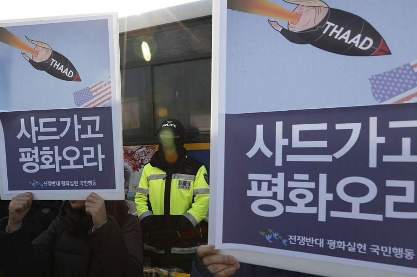 A South Korean policeman stands guard between protesters holding placards reading 'THAAD OUT' during a rally against the South Korean and the US government's defence policy in front of the Ministry of National Defence in Seoul.