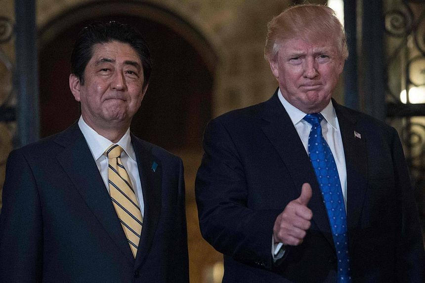 US President Donald Trump (right) gives the thumbs up next to Japanese Prime Minister Shinzo Abe at Trump's Mar-a-Lagoresort in Palm Beach, Florida, on Feb 11, 2017.