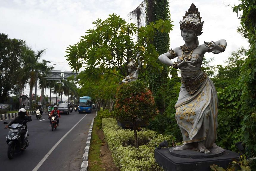 A Balinese statue is seen along a main road in Denpasar, Bali, on March 8, 2017.