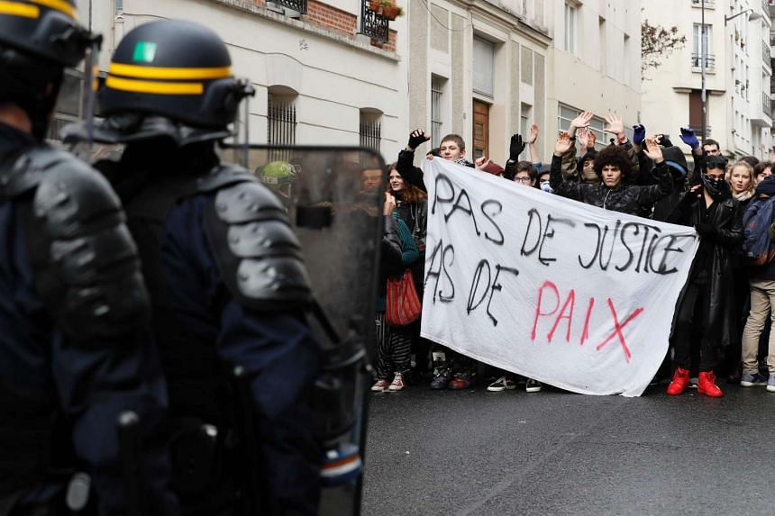 "High school students hold a banner reading ""No justice, No peace"" as they face anti riot police on Feb 28, 2017 in Paris."