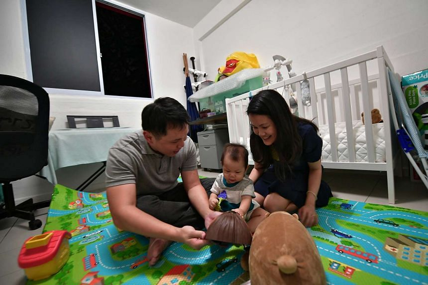 Mr Steve Tan and his wife Michelle Lee, playing with their son, Ryan Tan, in their PPHS rental flat at Commanwealth on March 6, 2017.