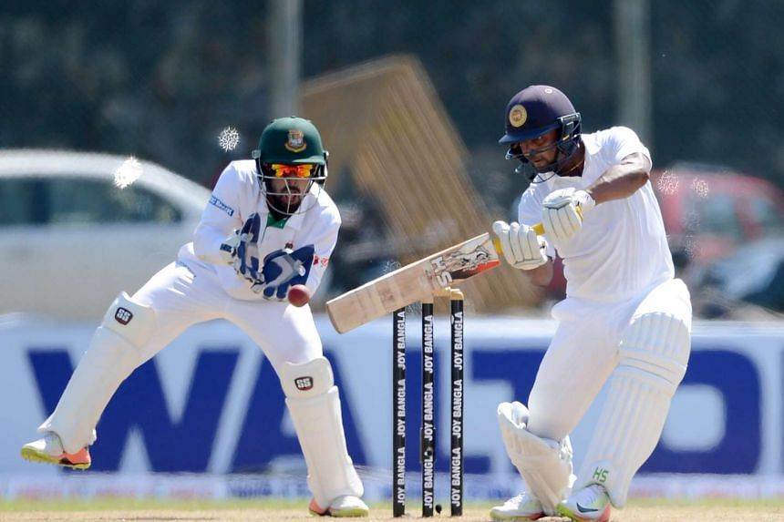 Sri Lankan cricketer Asela Gunaratne (right) is watched by Bangladesh wicketkeeper Liton Das as he plays a shot during the first day of the opening Test match between Sri Lanka and Bangladesh at the Galle International Cricket Stadium, on March 7, 20