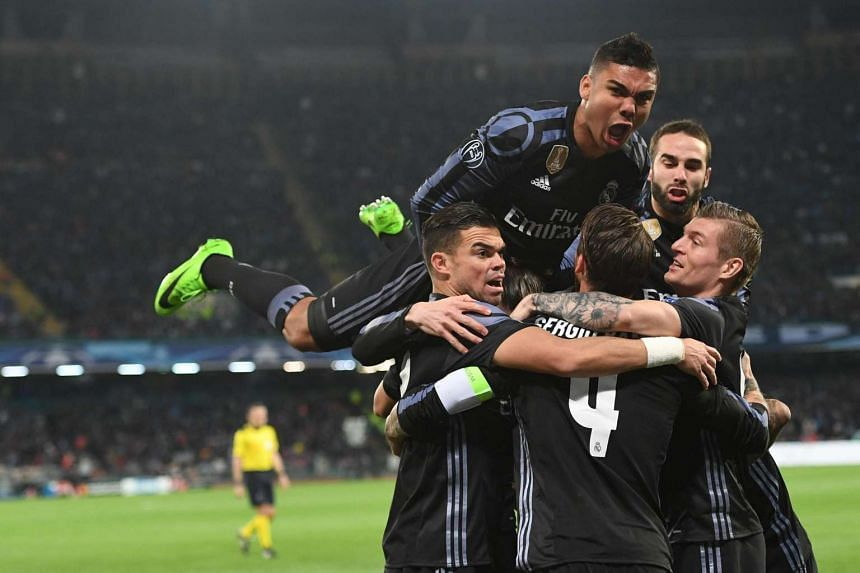 Real Madrid's Sergio Ramos (centre) celebrates with his teammates after scoring a goal during their Uefa Champions League round of 16 second leg football match against SSC Napoli.