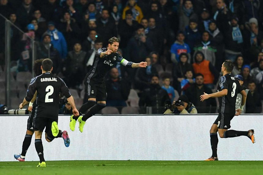 Real Madrid's defender Sergio Ramos (centre) celebrates after scoring during the UEFA Champions League football match SSC Napoli vs Real Madrid on March 7, 2017 at the San Paolo stadium in Naples.