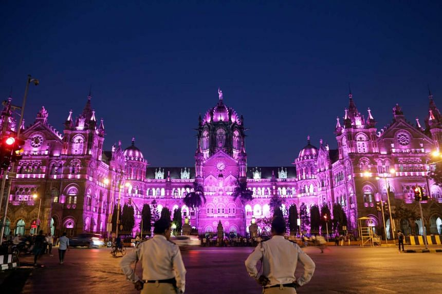 Traffic policemen stand in front of the Chhatrapati Shivaji Maharaj Terminus (CSMT) railway station, lit up in pink on the eve of International Women's Day, in Mumbai, India, on March 7, 2017.