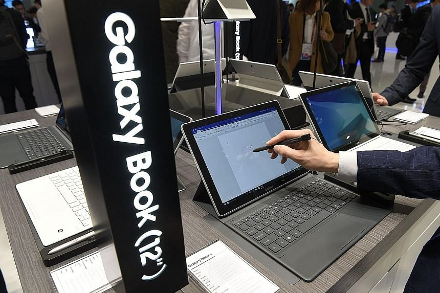 A visitor at the Barcelona show trying out Samsung's Galaxy Book, a tablet-laptop hybrid, which runs on Windows 10.