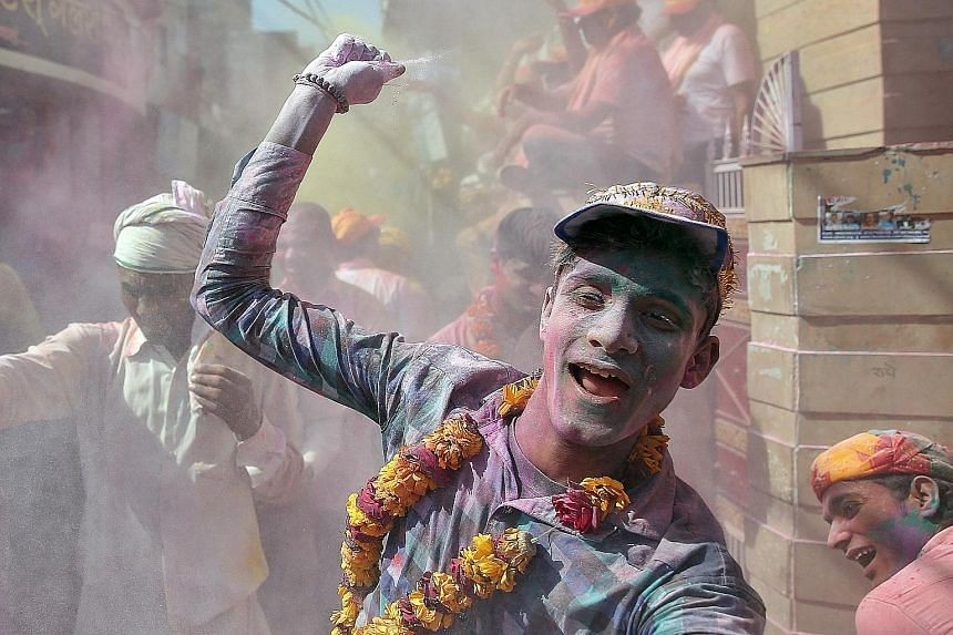 A man throwing coloured powder during Holi celebrations in the town of Barsana in the state of Uttar Pradesh in India on Monday. Holi is a Hindu festival that marks the arrival of spring. Known widely as the Festival of Colour, it takes place over tw