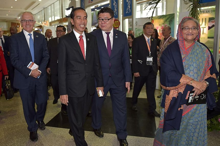 Both Mr Malcolm Turnbull and Mr Joko Widodo are wary of actions that could draw displeasure from Beijing. They are seen here at an exhibition on the sidelines of the Iora meeting. At far right is Bangladesh's Prime Minister Sheikh Hasina