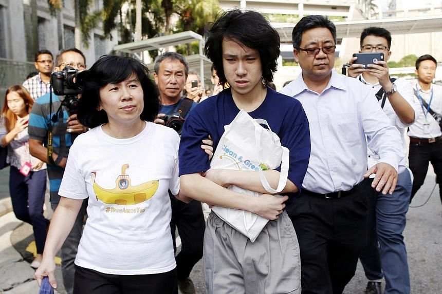 Teen blogger Amos Yee leaves with his parents after his sentencing from the State Courts in Singapore on July 6, 2015.
