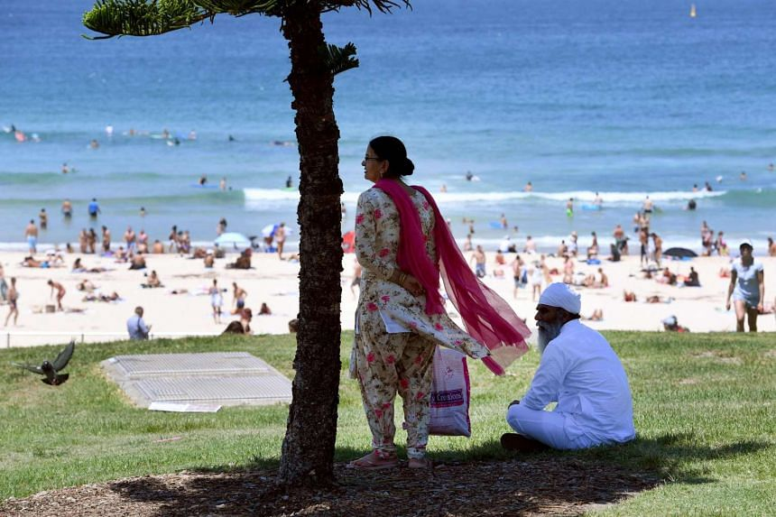 A couple taking shelter from the heat in the shade of a tree at Sydney's Bondi Beach on Feb 11, 2017.
