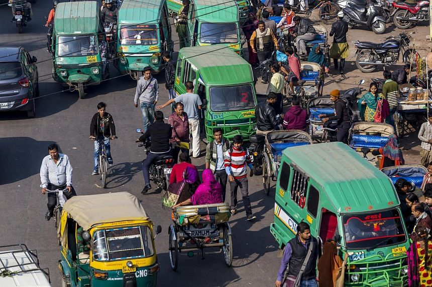Auto rickshaws waiting to pick up passengers at an intersection in Lucknow, Uttar Pradesh, India.