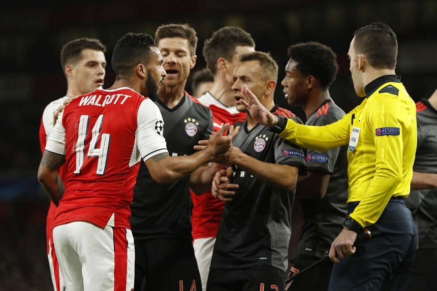 Arsenal's Theo Walcott clashes with Bayern Munich's Xabi Alonso, Rafinha and David Alaba after a penalty appeal.