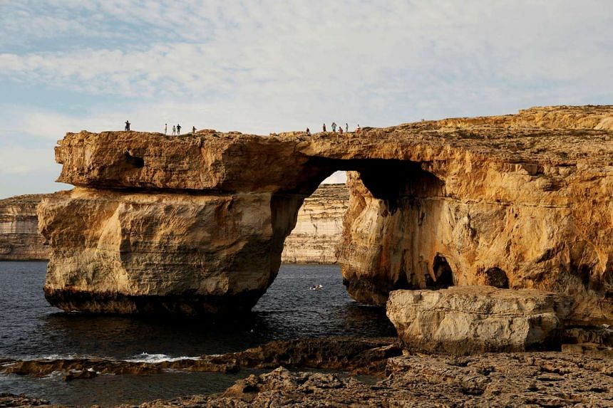 Tourists walk on the Azure Window, a 50m high rock arch, at Dwejra Point cliffs on the west coast of the Maltese island of Gozo.