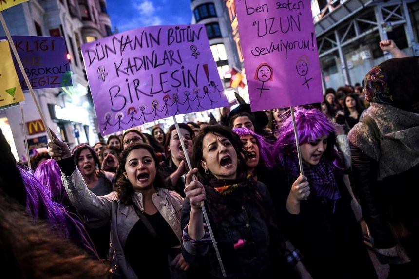 """People holding signs reading """"Get together all women of world"""" as they march down Istiklal Avenue in Istanbul on Wednesday (March 8)."""