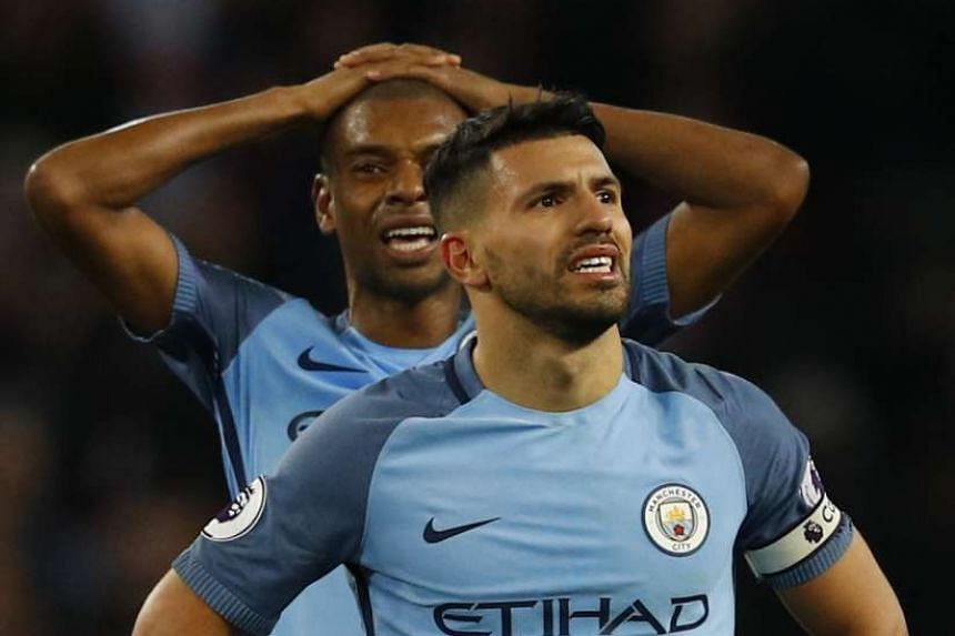 Manchester City's Sergio Aguero and Fernandinho look dejected after the game.