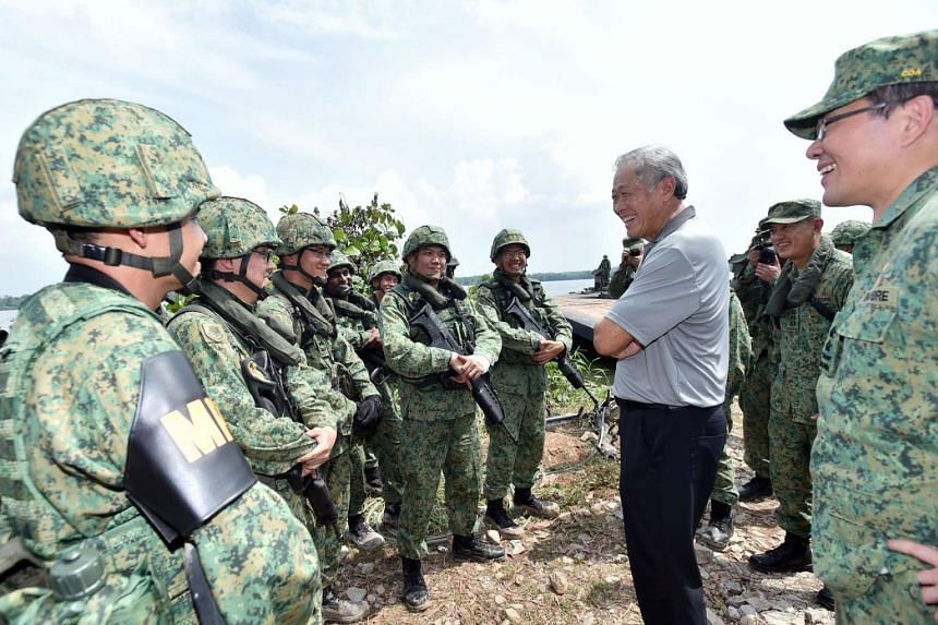 Defence Minister Ng Eng Hen (third from right), accompanied by Chief of Army Major-General Melvyn Ong (far right), interacting with NSmen participating in the SAF rafting exercise.