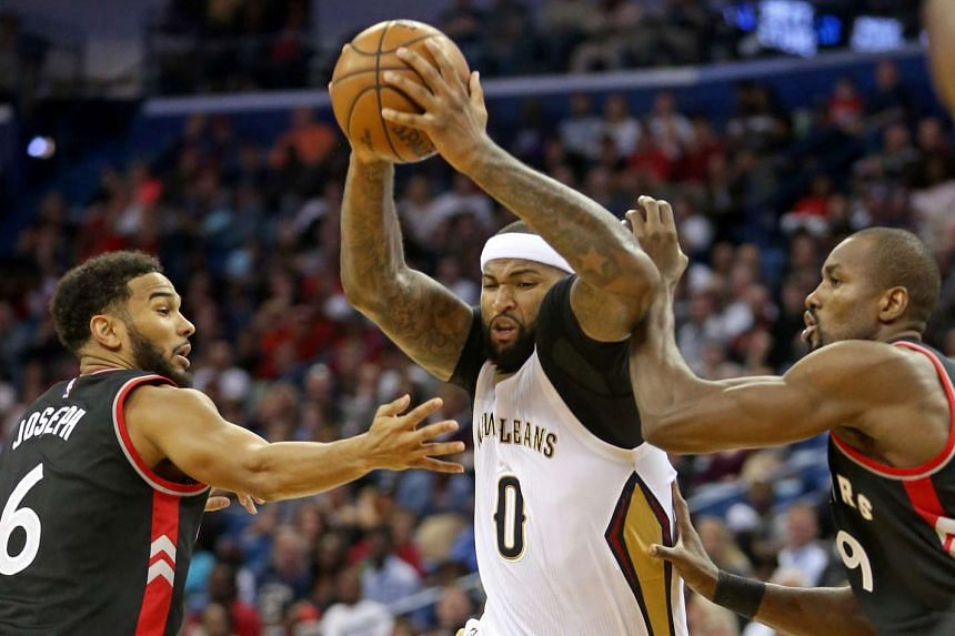 New Orleans Pelicans forward DeMarcus Cousins (0) drives between Toronto Raptors guard Cory Joseph (6) and forward Serge Ibaka (9) in the second half at the Smoothie King Center.
