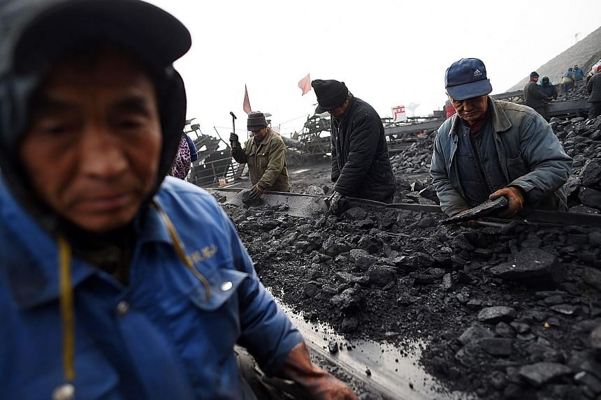 Chinese workers sort coal at a mine in Shanxi province. Coal imports tumbled to the lowest in nine months as demand weakened following the peak winter heating season. However, demand for commodities from iron ore to crude oil remains strong, resultin