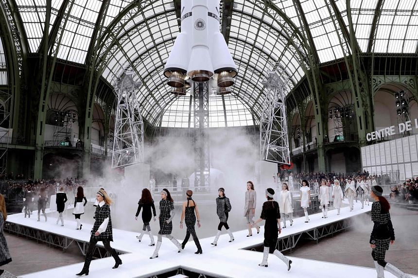 Chanel's collection, featuring glittery fashion from boots to quilted wraps (above), rolls out on a runway with a rocket as the focal point.
