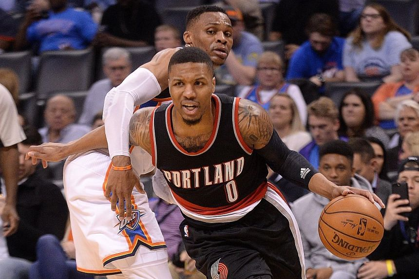 Portland guard Damian Lillard driving to the basket after evading a block by Oklahoma City guard Russell Westbrook. Seven Trail Blazers racked up double figures in their 126-121 win.