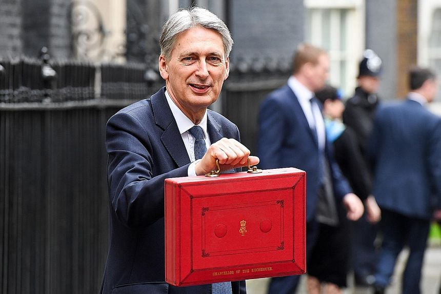 "Mr Hammond toting the Budget in a briefcase as he leaves his official residence at 11 Downing Street to present his first Budget statement. He says the fiscal plan lays the foundation for ""a stronger, fairer, more global Britain""."