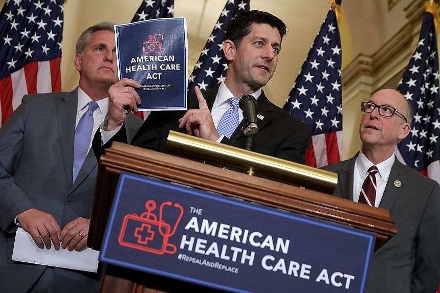 Mr Paul Ryan with a copy of the American Health Care Act at a news conference on Tuesday with House Majority Leader Kevin McCarthy (left) and House Energy and Commerce Committee chairman Greg Walden. Mr Ryan guaranteed he would drum up the 218 votes